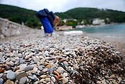 Ground-level close up of pebble beach, child (9 years old) bending over in background. Lapad Bay, Dubrovnik, Croatia