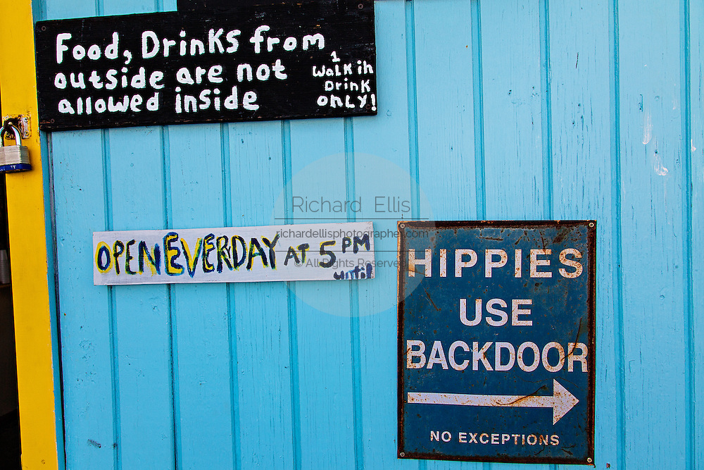 Old sign informing Hippies to use the backdoor at a bar on Green Turtle Cay, Bahamas.