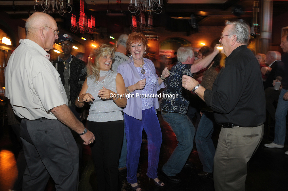 Friends Jim Allingham, 70, from left, Carol Ferrarelli, 60, Marilyn Whitley, 62, and Ed Whitley, 70, enjoy the late night dance scene at the Bourban St. bar in the main downtown square of The Villages, Fla., Saturday, Jan. 17, 2009. (Photo by Phelan M. Ebenhack)