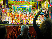 16 JANUARY 2015 - BANGKOK, THAILAND: An Chinese opera spectator photographs the Sai Yong Hong Opera Troupe at the Chaomae Thapthim Shrine, a Chinese shrine in a working class neighborhood of Bangkok near the Chulalongkorn University campus. The troupe's nine night performance at the shrine is an annual tradition and is the start of the Lunar New Year celebrations in the neighborhood. Lunar New Year, also called Chinese New Year, is officially February 19 this year. Teochew opera is a form of Chinese opera that is popular in Thailand and Malaysia.    PHOTO BY JACK KURTZ