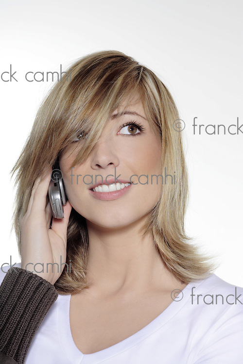 portrait in studio on a white background of a young blond caucasian smilling woman  holding a cell phone