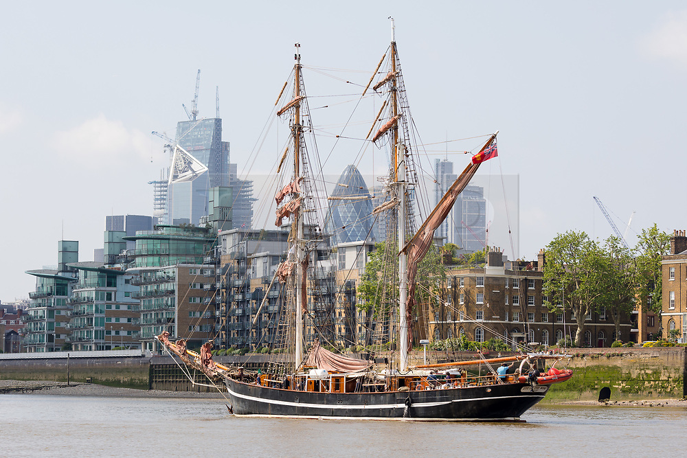 """© Licensed to London News Pictures. 23/05/2018. London, UK. The 107 year old tall ship, """"Eye of the Wind"""" sails on the River Thames in front of City of London skyscrapers during a London visit to join celebrations to mark forty years since the start of Operation Drake - a two year round the world expedition, of which Eye Of The Wind was the flagship. One of the last traditional sailing ships left, Eye of the Wind was originally built in Germany in 1911 as a Schooner but was given a new lease of life in 1973 when she was bought by Anthony """"Tiger"""" Timbs, an Englishman from greater London. A group of enthusiastic ship lovers began to rig the vessel as a brigantine and her full restoration at a shipard in Faversham, Kent took nearly four years to complete. Photo credit: Vickie Flores/LNP"""
