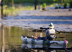 A bird watcher uses his camera from a kayak in order to get closer to the subject he is photographing