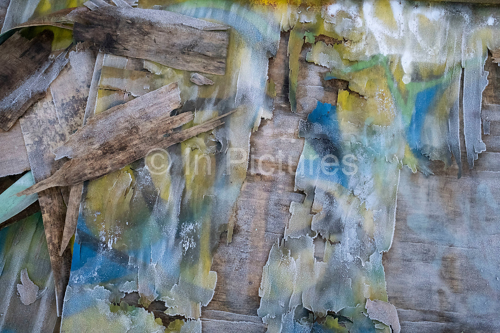 Frost crystals on graffiti covered wood on 7th January 2021 in Birmingham, United Kingdom. Frost is a thin layer of ice on a solid surface, which forms from water vapor in an above-freezing atmosphere coming in contact with a surface leaving crystal of water shimmering.