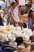 A family shops for a cowboy hat for their son at the Sunday market in Tlacolula de Matamoros, Mexico. The regional street market draws thousands of sellers and shoppers from throughout the Valles Centrales de Oaxaca.