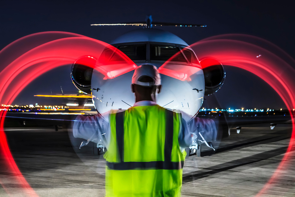Using high visibility red wands, a lineman simulates waving an aircraft into parking position at night.  Commissioned as advertising for Phillips 66 Aviation Fuels.<br />