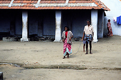 TAMIL NADU, MARCH 1994.A father is taking his daugther across the courtyard on a 'leash'. At the well she is going to be cleansed with 'holy water' which locals believe possess her body.