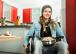 Young man with raw chicken in the pan, Munich, Bavaria, Germany