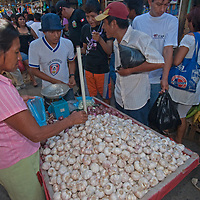 A merchant sells garlic in an outdoor market in upper Belem, a crowded neighborhood in Iquitos, Peru.