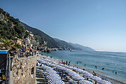 vacation beach with colorful rainbow chaise lounge chairs and umbrellas. resort beach. Monterosso al Mare, Cinque Terre, Italy