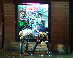 "© Licensed to London News Pictures . 23/12/2017. Manchester, UK. A man checks on the welfare of another , who gives two thumbs up as he sits in the window of a takeaway on Bootle Street , leaning over a pool of vomit between his feet . Revellers out in Manchester City Centre overnight during "" Mad Friday "" , named for being one of the busiest nights of the year for the emergency services in the UK . Photo credit: Joel Goodman/LNP"