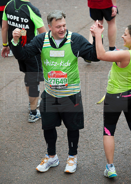 © London News Pictures. 22/04/2012. London, UK. Labour MP Ed Balls gives a high five to another runner after crossing the finnish line at the 2012 Virgin London Marathon in London on April 22, 2012. Photo credit : Ben Cawthra /LNP