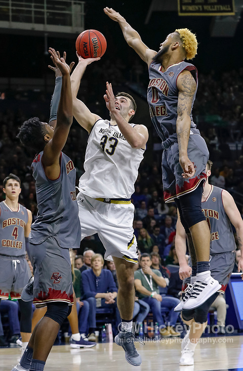 SOUTH BEND, IN - JANUARY 12: John Mooney #33 of the Notre Dame Fighting Irish shoots the ball as Ky Bowman #0 of the Boston College Eagles reaches to block at Purcell Pavilion on January 12, 2019 in South Bend, Indiana. (Photo by Michael Hickey/Getty Images) *** Local Caption *** John Mooney; Ky Bowman