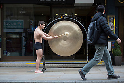 © licensed to London News Pictures. London, UK 22/11/2012. Chris Rowley, the winner of new Rank films 'Gongman', banging a gong outside Grosvenor G Casino in London. Photo credit: Tolga Akmen/LNP