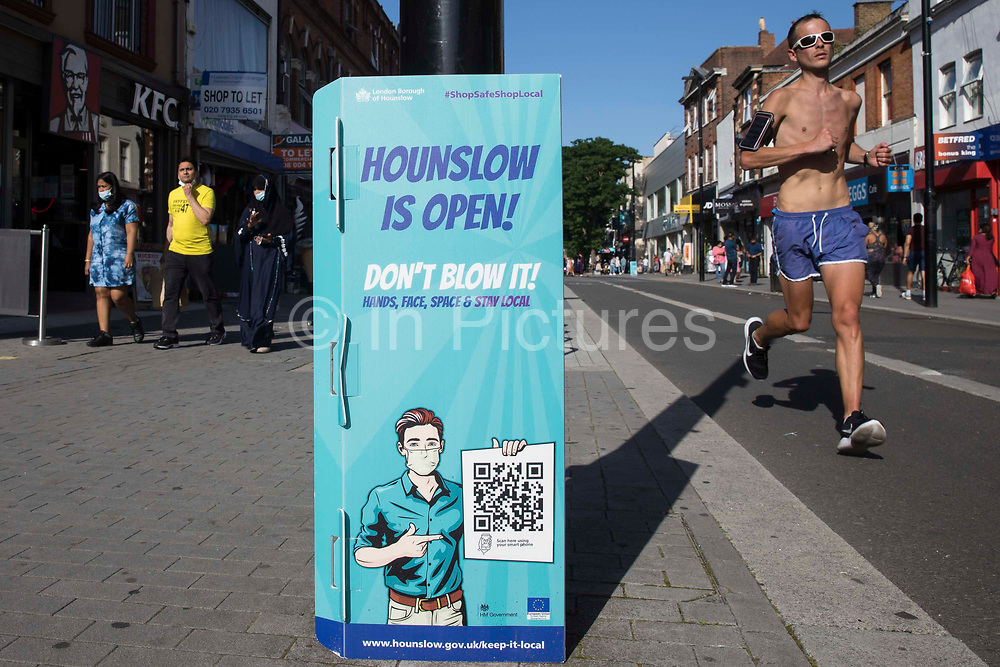 A runner passes a London Borough of Hounslow Covid-19 public information sign urging residents to take precautions to minimise the spread of the coronavirus amid rising concern regarding the Delta variant on 17th July 2021 in Hounslow, United Kingdom. The UK government is currently still expected to lift almost all restrictions on social contact on 19th July, known as Freedom Day, but the current wave driven by the Delta variant is not expected to peak until mid-August.