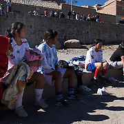 'Attitude at Altitude' Football in Potosi, Bolivia'..Girls breast feed and rest during half time during the Liga Deportiva San Cristobal finals matches on the stone and gravel surface high in the hills over Potosi. Potosi, Bolivia 9th May 2010..'Attitude at Altitude' Football in Potosi, Bolivia'..The Calvario players greet the final whistle with joyous celebration, high fives and bear hugs the players are sprayed with local Potosina beer after a monumental 3-1 victory over arch rivals Galpes S.C. in the Liga Deportiva San Cristobal. The Cup Final, high in the hills over Potosi. Bolivia, is a scene familiar to many small local football leagues around the world, only this time the game isn't played on grass but a rock hard earth pitch amongst gravel and boulders and white lines that are as straight as a witches nose, The hard surface resembles the earth from Cerro Rico the huge mountain that overlooks the town. .. Sitting at 4,090M (13,420 Feet) above sea level the small mining community of Potosi, Bolivia is one of the highest cities in the world by elevation and sits 'sky high' in the hills of the land locked nation. ..Overlooking the city is the infamous mountain, Cerro Rico (rich mountain), a mountain conceived to be made of silver ore. It was the major supplier of silver for the spanish empire and has been mined since 1546, according to records 45,000 tons of pure silver were mined from Cerro Rico between 1556 and 1783, 9000 tons of which went to the Spanish Monarchy. The mountain produced fabulous wealth and became one of the largest and wealthiest cities in Latin America. The Extraordinary riches of Potosi were featured in Maguel de Cervantes famous novel 'Don Quixote'. One theory holds that the mint mark of Potosi, the letters PTSI superimposed on one another is the origin of the dollar sign...Today mainly zinc, lead, tin and small quantities of silver are extracted from the mine by over 100 co operatives and private mining companies who still mine the mountai