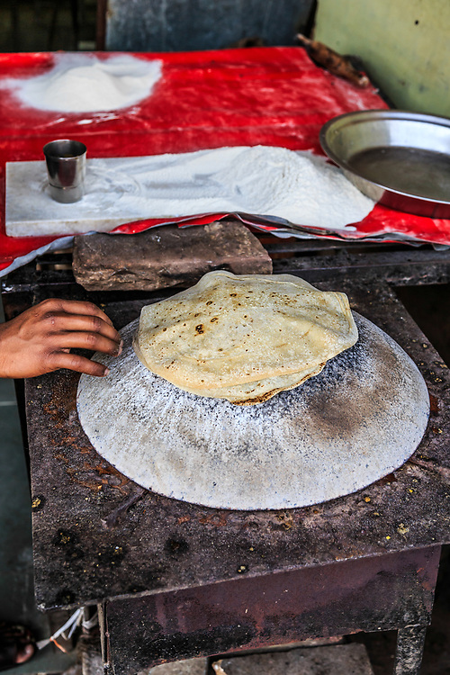 Making Chapati bread  in Old Town in New Delhi, India. Indian chapati is a bread made of whole wheat flour. It is usually served with a curry, but it is very versatile. It can be used just like regular toast, or as a side to many dishes.