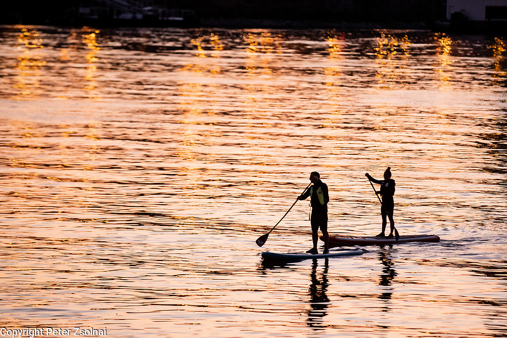 SUP riders paddle during sunset on the river Danube in Budapest, Hungary.