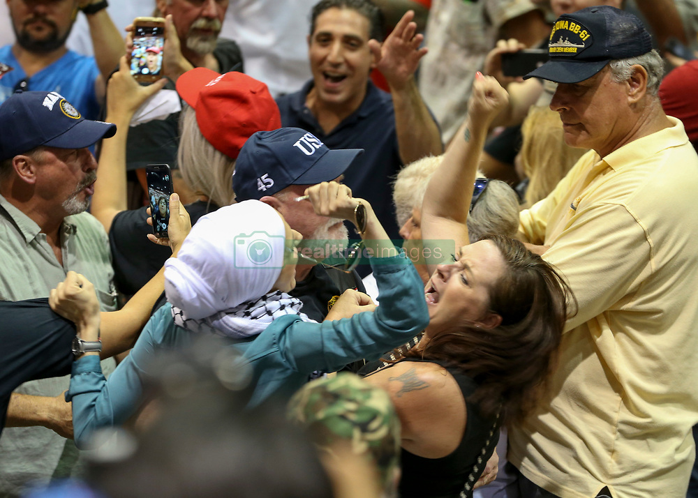 July 31, 2018 - Tampa, Florida, U.S. - AIDA MACKIC, a 35-year-old Tampa mother of four, is removed from President Donald Trump's rally at the Florida State Fairgrounds on Tuesday. Mackic, a Muslim woman who wears a traditional head scarf, was one of six women who shouted, 'Immigrant rights are human rights.' 'I didn't think I'd experience that much anger from humans who don't even know me,' Mackic, a 35-year-old married mother of four who immigrated to the United States as a child from war-torn Bosnia, said during an interview Wednesday. (Credit Image: © Chris Urso/Tampa Bay Times via ZUMA Wire)