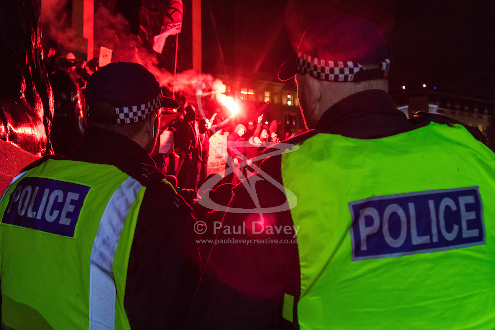 London, November 5th 2016. Anti-capitalists and anarchists participate in the Million Mask March, an annual event that happens on November 5th each year in cities across the world, as part of a protest against the establishment. Many of the protesters wear Guy Fawkes masks, often associated with the internet activism group Anonymous. PICTURED: Riot police keep watch as activists burn a flare on the plinth of Nelson's Column in Trafalgar Square.