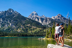 An attractive couple taking in the wonders of the Grand Tetons at Taggart Lake in Grand Teton National Park.