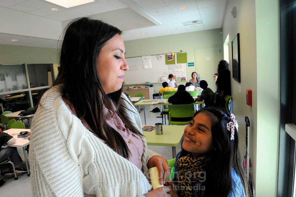 """Carissa Purnell, left, and Michelle Mora, 10, during the Cesar Chavez Library's supervised study and activities program. The program includes snacks, and is funded by a """"Building Healthy Communities"""" grant organized by Carissa Purnell, manager of technology for the library."""