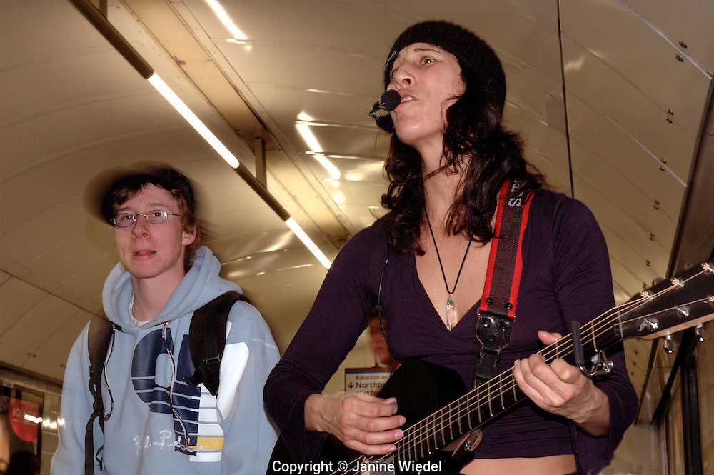 Young female busker playing guitar and singing down the underground in London.
