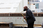 Brooklyn, NY - 7 May 2021. The Brooklyn Academy of Music (BAM) started a series of its first live concerts since the COVID pandemic lockdown in conjunction with the Silk Road Project at several sites in the Brooklyn Navy Yard. The 10-minute 1-to-1 concerts feature a single performer playing for a single audience member. Saxophonist Danny Mekonnen on the roof of Building 280.