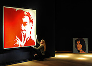 London News pictures. 08.02.2011. A woman holds a rediscovered self-portrait by Andy Warhol. The picture painted in 1967 which has been in a private collection since 1974 is expected to realise 3 million to 5 million pounds. In the background is A warhol painting of Mick Jagger, expected to fetch 550.00-750.00- pounds. A preview, today (Fri) of Christie's Auction House Post-War and Contemporary Art Evening Auction. The sale is expected to make a combined total of 46,246,000 to 66,447,000 when it is sold on 16th Feb 2011.. Picture Credit should read Stephen Simpson/LNP