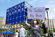 """Wilkes-Barre, PA (July 11, 2020) -- A woman holds a """"No Justice/No Peace"""" sign at the Black Lives Matter NEPA United Movement demonstration at Wilkes-Barre Public Square."""