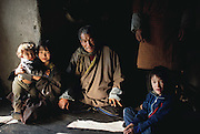 Namgay with his daughter Zekom, right, and his granddaughter Choeden and baby grandson Wangchuck in the kitchen of their home in Shingkhey, Bhutan. From coverage of revisit to Material World Project family in Bhutan, 2001.
