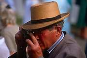 An elderly gentleman takes a photo using a 35mm film camera during the annual Chelsea Flower Show in London. The elderly man peers at the world through his camera's viewfinder to see the world within a small aperture, to record his view of the scenes using the analogue film system, a decade before the arrival of digital imaging technology.
