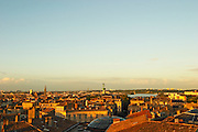 A view over the rooftops and city of Bordeaux with the Pont d'Aquitaine over the Garonne river at sunset