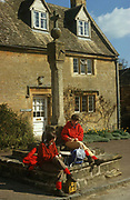 Two women country walkers stop on their day's trek across the Cotswolds in the village of Stanton. Wearing red sweaters and matching coloured socks, the two ladies have stopped to snack on the steps of the medieval cross outside a Cotswolds stone cottage in the main high street. Stanton is probably one of the prettiest and idyllic villages in the whole of the Cotswolds. Little changed in 300 years it nestles beneath the slopes of Shenbarrow Hill. It has a very pleasing long main street with several delightful corners where the ancient house are built in typical Cotswolds style with steeply pitched gables, mullioned windows and glowing honey coloured limestone walls. The village contains a number of 16th and 17th century houses as well as a restored, medieval cross and a church in which some Norman work is still evident.