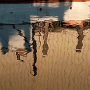 Reflections of a commercial fishing boat in Gloucester Harbor, Massachusetts