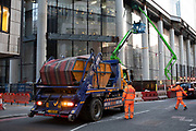Workers stop traffic to allow a skip to reverse onto the road on a construction site use tall cherry pickers to work on a new skyscraper in the City of London on 5th February 2020 in London, England, United Kingdom. The City of London is a city, county and a local government district that contains the historic centre and the primary central business district CBD of London.