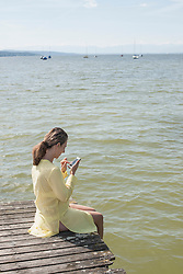 Woman using smart phone and sitting on jetty at the lake, Ammersee, Upper Bavaria, Germany