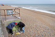 Volunteers scrub graffiti sprayed on a seafront steps on the beach, on 3rd May 2021, in St Leonards, Sussex, England.
