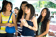 Teenage girls exploring the rich heritage of the Hmong cuisine. Hmong Sports Festival McMurray Field St Paul Minnesota USA