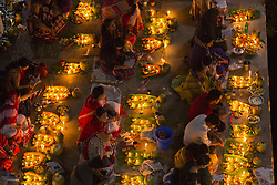 November 3, 2018 - Dhaka, Bangladesh - DHAKA, BANGLADESH - NOVEMBER 03 :  Hundreds of Hindu devotees sits with Prodip and prays to God in front of Shri Shri Lokanath Brahmachari Ashram temple during the Kartik Brati or Rakher Upobash in Dhaka , Bangladesh on November 03, 2018...Every year thousands of Hindu devotees gather in front of Shri Shri Lokenath Brahmachari Ashram temple for the Kartik Brati or Rakher Upobash religious festival in Dhaka, Bangladesh. Faithful sit in front of candles light ( named locally as Prodip ) and absorb in prayer..Lokenath Brahmachari who is called Baba Lokenath was an 18th Century Hindu saint and philosopher in Bengal. Hindu worshippers fast and pray in earnest to the gods for their favors during the traditional ritual called Kartik Brati or Rakher Upobash..Lokenath Brahmachari devotees pray with light to save their family and dear from cholera and pox disease. (Credit Image: © Zakir Hossain Chowdhury/ZUMA Wire)