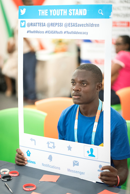 5 December 2017, Abidjan, Côte d'Ivoire: A man poses with an Instagram photo frame at a youth booth in the Global Village area of ICASA 2017. The 19th International Conference on AIDS and STIs in Africa (ICASA) 2017 gathers thousands of researchers, medical professionals, academics, activists and faith-based organizations from all over the world, all looking to overcome the HIV epidemic and eliminate AIDS as a public health threat.