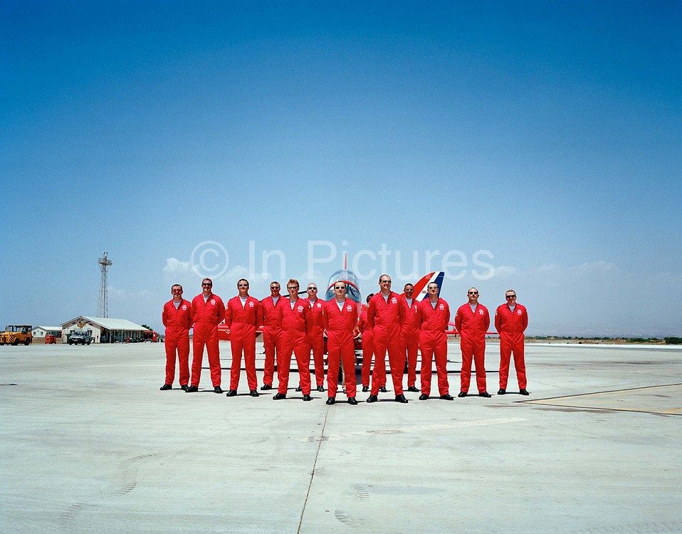 Official publicity portrait for the Red Arrows, Britain's RAF aerobatic team in mid-day glare at RAF Akrotiri. In the mid-day heat, all members of the elite 'Red Arrows', Britain's prestigious Royal Air Force aerobatic team, stand at ease and we see the back of one of the squadron's official photographers head, looking into the viewfinder of his camera to record an official photograph immediately on PDA Day at RAF Akrotiri, Cyprus. PDA (or 'Public Display Authority'), is when they are allowed by senior RAF officers to perform as a military aerobatic show in front of the public - following a special test flight when their every move and mistake is assessed and graded. Until that day arrives, their training and practicing is done in the privacy of their own airfield at RAF Scampton in Lincolnshire, UK or here in the glare of Akrotiri.