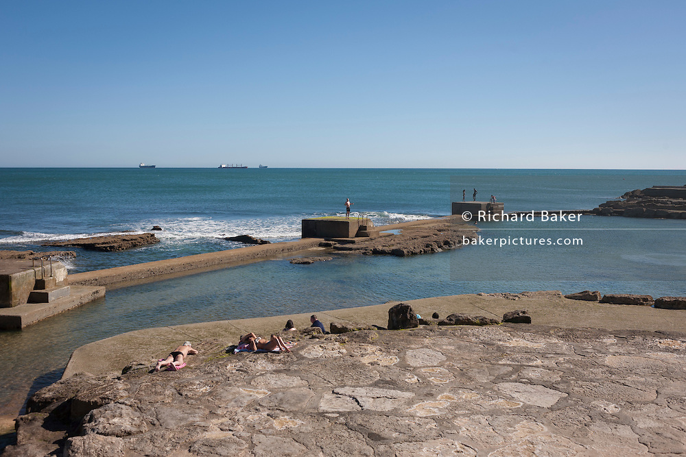 A wide panorama looking at to sea, of sunbathers and waves at Estoril near Lisbon, Portugal.