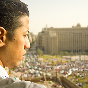 Hotelier overlooks a Tahrir Square protest from Sun Hotel. Cairo, Egypt.