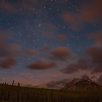 Alpenglow lingers on clouds and mountains in the Canadian Rockies.