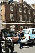 Press photographer at work in Whitehall during the London Taxi strike over the Uber mobile App. Using a camera on a 5 metre boom pole controlled from his mobile phone. Thousands of London's Black Cabs  brought parts of central London to a standstill. Whitehall, Central London, 11th June 2014