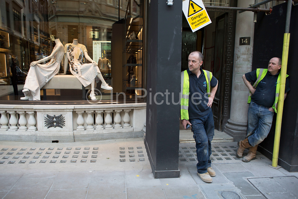 Two workmen taking a break outside a shop refit on New Bond Street, London, UK. The two men seem to be mirroring a pair of mannequins in the shop window display next to them.