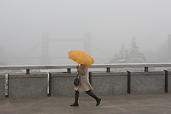 © Licensed to London News Pictures. 11/05/2016. LONDON, UK.  A woman with an umbrella walks across London Bridge in London during foggy and wet weather this morning.  Tower Bridge and HMS Belfast which are normally visible behind are disappearing in the fog. Photo credit: Vickie Flores/LNP