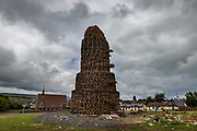 A large bonfire in Larne, all ready for the midnight festivities to begin. In the distance the largest bonfire in Belfast can be seen, Craigyhill. Belfast, NI, 2021.