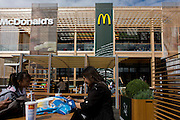 Spectators dine outside the world's biggest McDonald's in the Olympic Park during the London 2012 Olympics. Hundreds of food outlets at Olympic venues have been forced to take chips off the menu, because of a demand from sponsor McDonald's. Olympic chiefs banned all 800 food retailers at the 40 Games venues across Britain from dishing up chips because of 'sponsorship obligations. This land was transformed to become a 2.5 Sq Km sporting complex, once industrial businesses and now the venue of eight venues including the main arena, Aquatics Centre and Velodrome plus the athletes' Olympic Village. After the Olympics, the park is to be known as Queen Elizabeth Olympic Park.